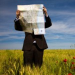 businessman lost in field using a map