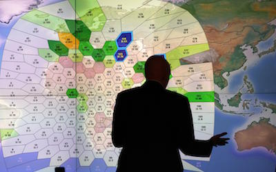 A member of staff at satellite communications company Inmarsat works in front of a screen showing subscribers using their service throughout the world, at their headquarters in London